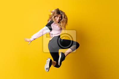 Obraz Urban Ballerina dancing over isolated yellow background and jumping