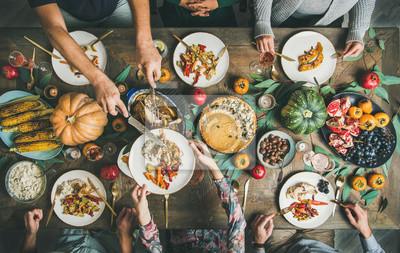 Obraz Uroczysta impreza z okazji Święta Dziękczynienia. Flat-lay przyjaciół lub rodziny jedzące różne przekąski i indyka na świątecznym stole świątecznym, widok z góry