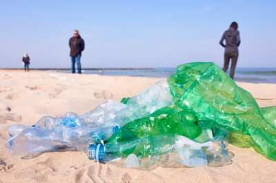 Used plastic bottles left on a beach by tourists, selective focus.