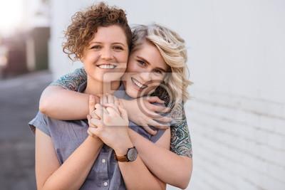 Obraz Uśmiechnięta młoda lesbian para stoi czule wpólnie outdoors