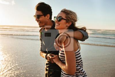 Obraz Uśmiechnięta młoda para chodzenia na plaży
