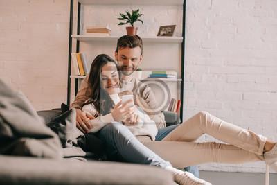 Obraz uśmiechnięta młoda para razem za pomocą smartfona na kanapie w domu