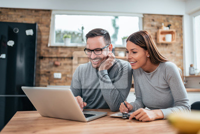 Obraz Uśmiechnięta para używa laptop przy kuchennym stołem.