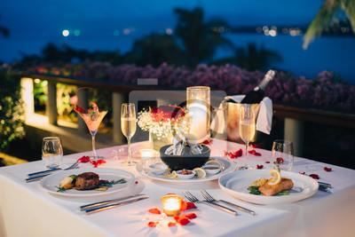 Obraz Ustawienie romantycznego stołu przy świecach na Walentynki z szampanem i kieliszkami do wina oraz specjalnymi potrawami