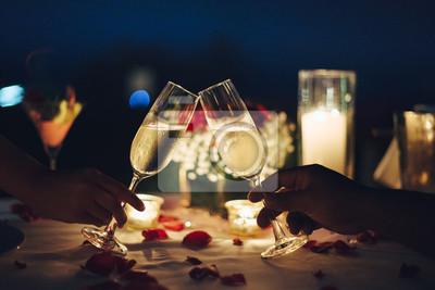 Obraz Ustawienie stołu romantycznego przy świecach. Mężczyzna i kobieta trzymają kieliszek Champaign.