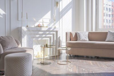 Obraz very light and bright interior of luxurious cozy living room with chic soft beige furniture with gold metallic elements, huge window to the floor and wooden parquet