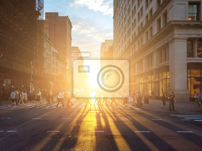 View of a busy intersection in Manhattan with sunlight shining on crowds of people in New York City