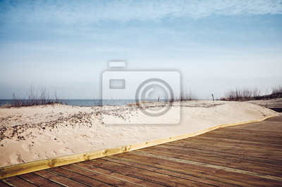 View of a wooden boardwalk by a beach, color toned picture.