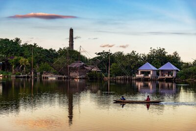 View of roral people with boat in river and sunset countryside