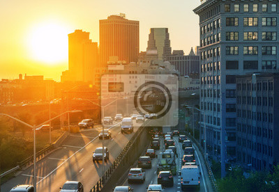 View of rush hour traffic on the Brooklyn Queens Expressway in New York City with sunset background