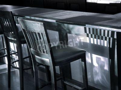 Vintage drewniany bar stolcu rzuca cień na pasku w stonowanych niebiesko-czarno-białe zdjęcia.