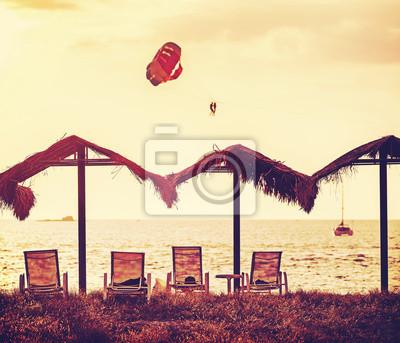 Vintage filtrowany obraz plaży i paralotniarzy na zachód słońca.