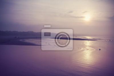 Vintage filtrowany obraz plaży o zachodzie słońca.