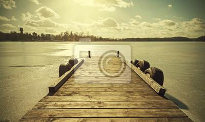 Vintage retro stonowanych obraz molo na zamarzniętym jeziorze.