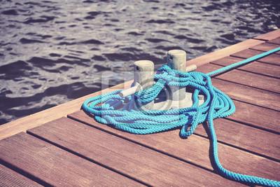 Vintage stonowanych obraz klucza z niebieską liną na drewnianym molo, płytkie głębi pola.