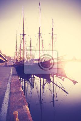 Vintage stylizowane łodzie żaglowe o zachodzie słońca.