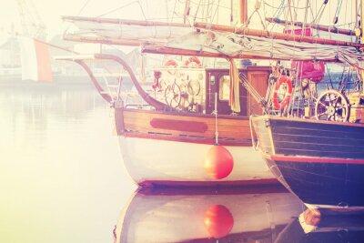Vintage stylizowane zdjęcia starych łodzi żaglowych na wschód słońca.