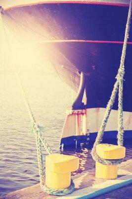 Vintage stylizowane żółty pachołek trzyma statek zacumowany.