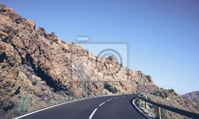 Vintage toned scenic winding mountain road seen through the windshield, Tenerife, Spain.