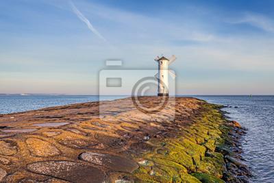Vivid sunrise over pier and lighthouse in Swinoujscie.