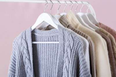 Obraz Warm knitted clothes hanging on a rack