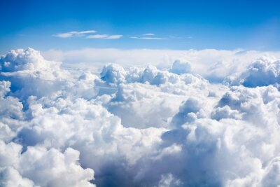 Obraz White clouds on blue sky background close up, cumulus clouds high in azure skies, beautiful aerial cloudscape view from above, sunny heaven landscape, bright cloudy sky view from airplane, copy space