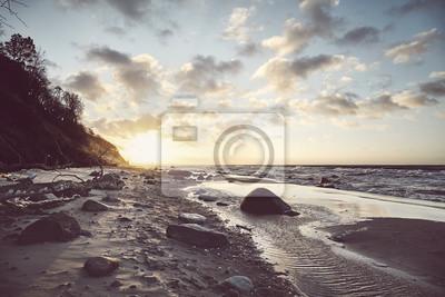 Widok na malowniczą plażę o zachodzie słońca, zastosowano tonację kolorów.