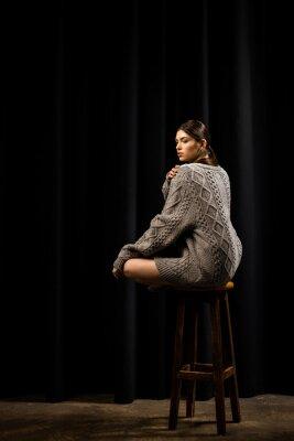 widok z boku młodej kobiety w wełniany szary sweter, siedząc na stołku barowym na czarnym tle