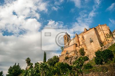 Widok z dołu Kościół parafialny z najczystszych Poczęcia z błękitne niebo i szare chmury burzowe. Kościół jest w Zufre, górskiej miejscowości Huelva, Hiszpania