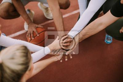 Obraz Widok z góry drużyny koszykówki, trzymając się za ręce nad sądem