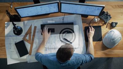 Obraz Widok z góry inżyniera architekta pracuje nad jego plany, trzymając komputer typu Tablet, przy użyciu komputera stacjonarnego również. Jego biurko jest pełne przydatnych przedmiotów i wieczornego słoń
