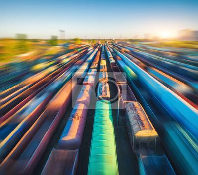 Widok z lotu ptaka kolorowi pociągi towarowi przy zmierzchem. Wagony towarowe z towarami na stacji kolejowej. Popędzać. Przemysł ciężki. Przemysłowy krajobraz z platformą kolejową. Widok z góry z dron