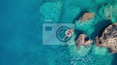 Obraz Widok z lotu ptaka na dziewczynę na powierzchni morza. Piękny skład w okresie letnim