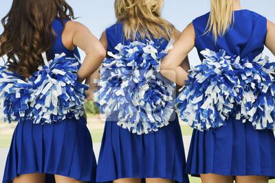 Obraz Widok z tyłu brzuch trzech cheerleaders posiadających pompony