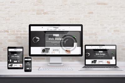 Obraz Wiele urządzeń wyświetlających z nowoczesną witryną internetową o płaskiej konstrukcji. Drewniane biurko i wnętrze ceglanego muru.