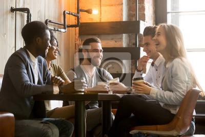 Obraz Wielorasowe przyjaciele bawią się i śmieją się pić kawę w kawiarni, różnorodni młodzi ludzie rozmawiają żartując razem przy stoliku kawiarnianym, wielu etnicznych millenialistów spędzających czas w ka