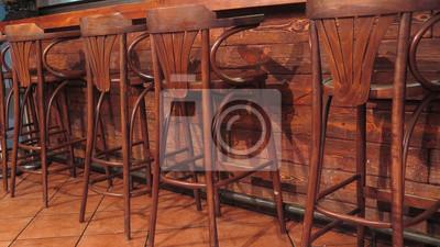 Wiersz pustych drewnianych stołków barowych