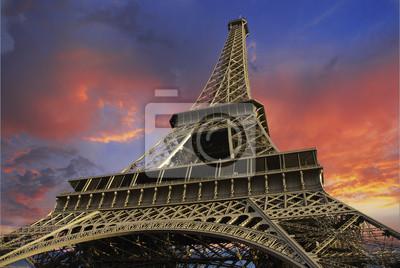 Wieża Eiffla o zachodzie słońca na tle zachmurzonego nieba