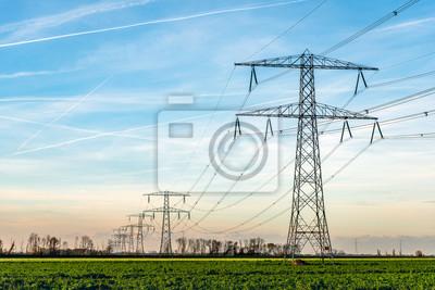 Obraz Wieże wysokiego napięcia z grubymi wiszącymi kablami zasilającymi w wiejskim krajobrazie w Holandii