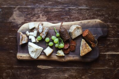 Obraz Wine appetizers set: meat and cheese selection, grapes, bread on