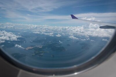 Obraz Wing of airplane flying above Hong Kong city background through the window.