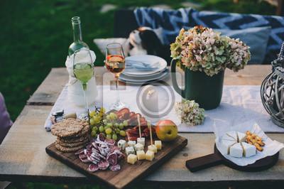 Obraz wino, ser, szynka i owoce podawane na drewnianej desce do krojenia. Letnia impreza w ogrodzie na świeżym powietrzu