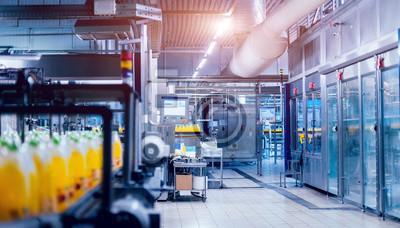 Obraz Wnętrze fabryki napojów. Przenośnik z butelkami do soku lub wody. Sprzęt