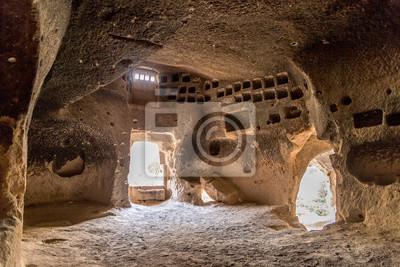 Obraz Wnętrze kościoła z ołtarzem i malowanymi dekoracjami na ścianie starożytnego miasta z domami jaskiniowymi wykutymi w skałach wulkanicznych z drzwiami i oknami, Kapadocja