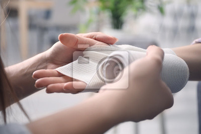 Obraz Woman applying bandage onto female wrist, closeup