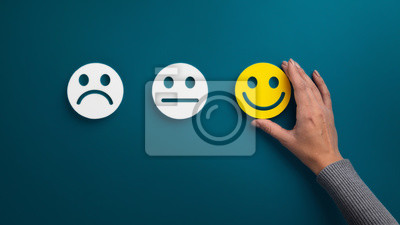 Obraz Woman choosing happy smiley face emotion on green