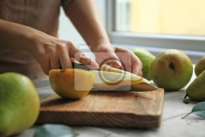 Obraz Woman cutting ripe pears on table
