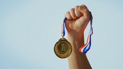 Obraz woman hand raised, holding gold medal against sky. award and victory concept