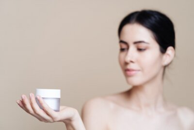 Obraz Woman holds jar of cream. Photo of pretty woman with perfect skin on beige background. Beauty product presentation