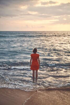 Woman in orange dress stands still in the ocean at sunset, color toning applied.